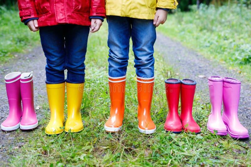 Kleine jonge geitjes, jongens en meisjes in kleurrijke regenlaarzen Kinderen die zich in de herfst bosclose-up bevinden van schoo royalty-vrije stock afbeelding