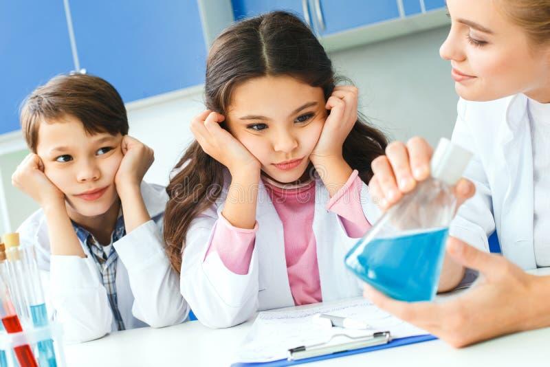 Kleine jonge geitjes met leraar in boring les van het schoollaboratorium stock afbeeldingen