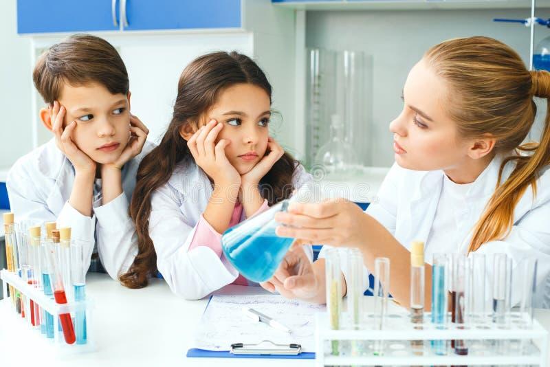 Kleine jonge geitjes met leraar in de les van het schoollaboratorium explainig stock foto's