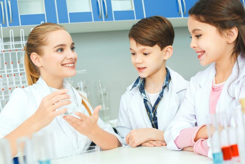Kleine jonge geitjes met leraar in de lessenverklaring van het schoollaboratorium stock afbeelding