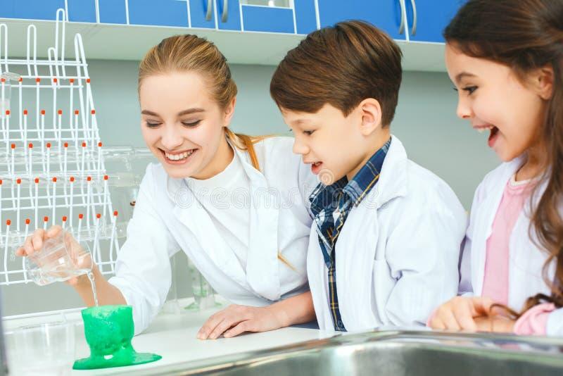 Kleine jonge geitjes met leraar in de zure reactie van het schoollaboratorium stock afbeelding