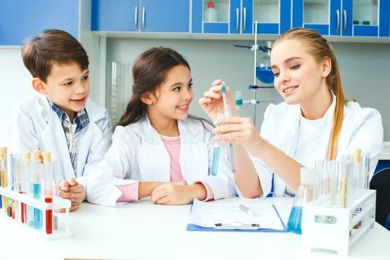 Kleine jonge geitjes met leraar die in schoollaboratorium reactie verklaren stock foto