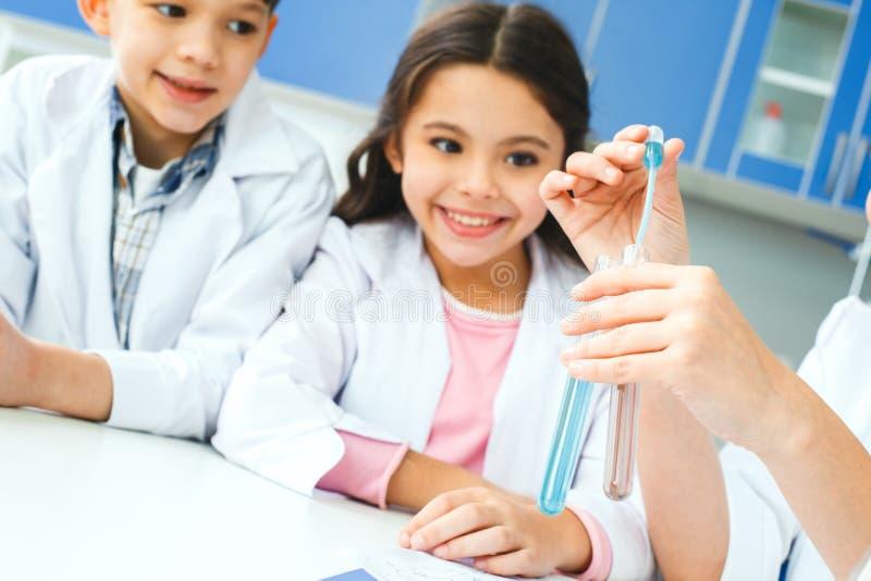 Kleine jonge geitjes met leraar die in schoollaboratorium vloeistoffenclose-up mengen royalty-vrije stock foto's