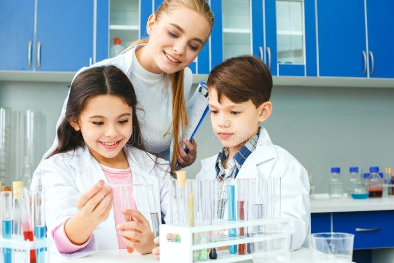 Kleine jonge geitjes met leraar in het experiment van het schoollaboratorium stock afbeeldingen