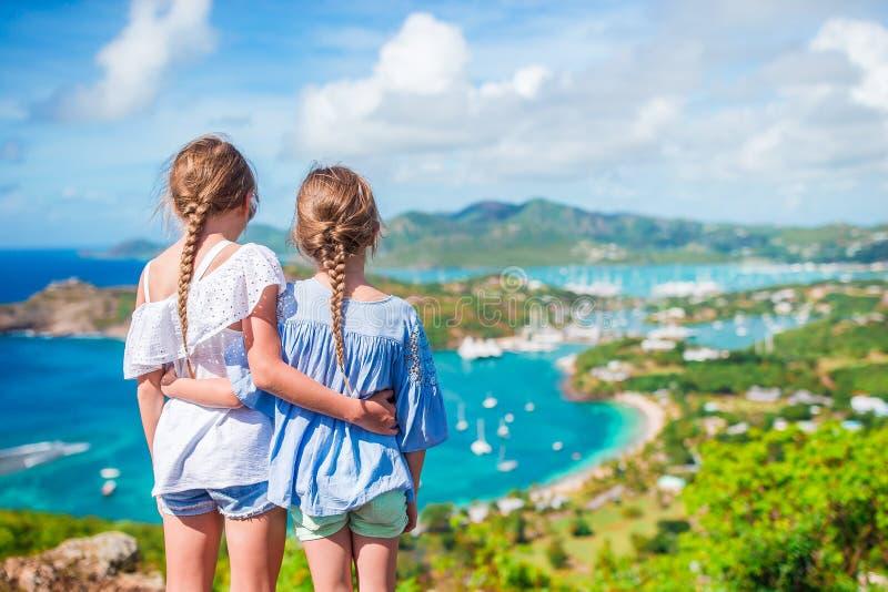 Kleine jonge geitjes met mooie beroemde mening Mening van Engelse Haven van Shirley Heights, Antigua, paradijsbaai bij tropisch royalty-vrije stock afbeeldingen