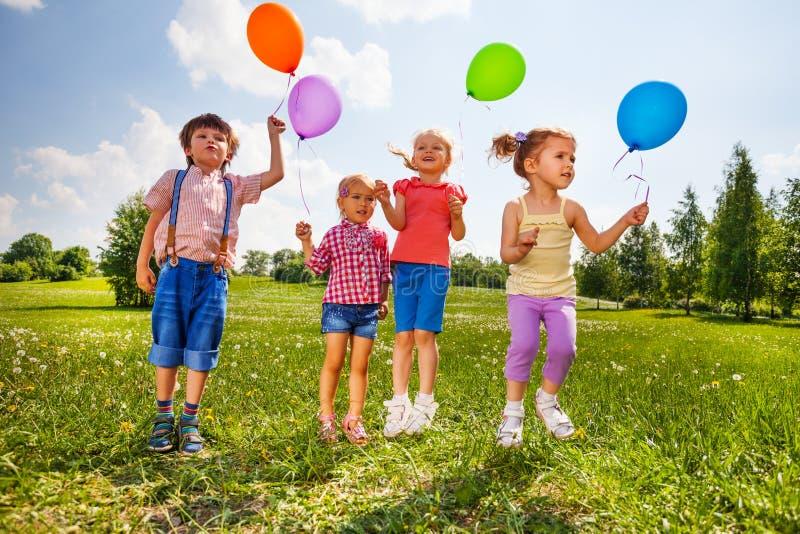 Kleine jonge geitjes met vier ballons in groene weide royalty-vrije stock foto's