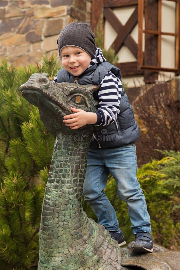 Kleine jongen dichtbij een steenbeeldhouwwerk van een draak stock afbeelding