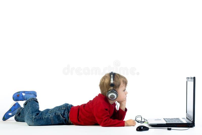 Kleine jongen die aan muziek luistert stock fotografie
