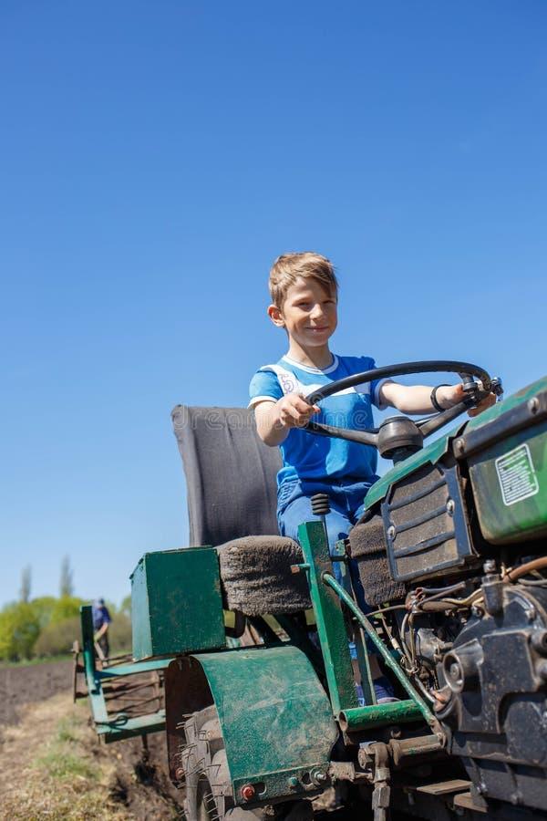 Kleine jongen die probeert een tractor op het veld te rijden stock fotografie