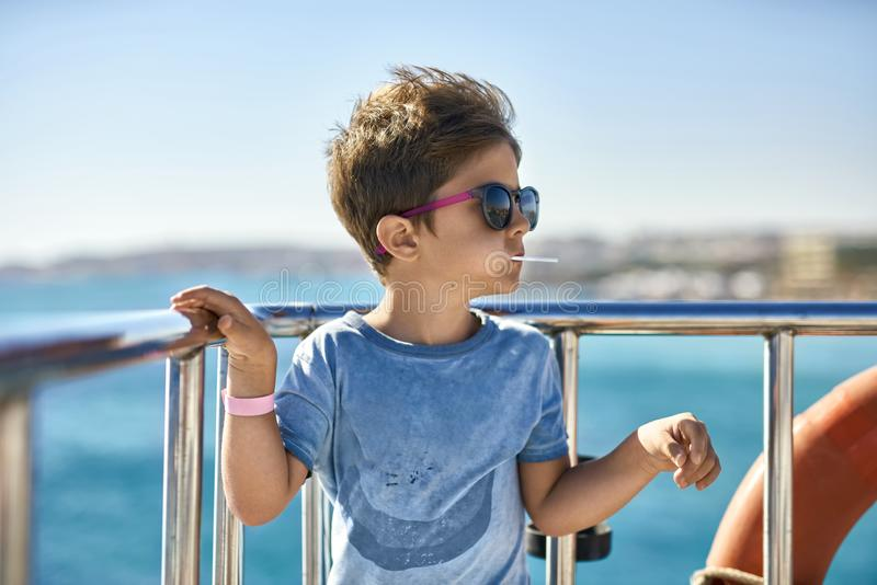 Kleine jongen die in zonnebril lolly op jachtdek eten stock foto's