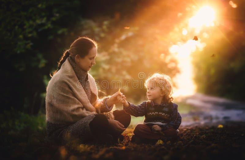 Kleine jongen en zijn moederzitting in herfstbos royalty-vrije stock foto's