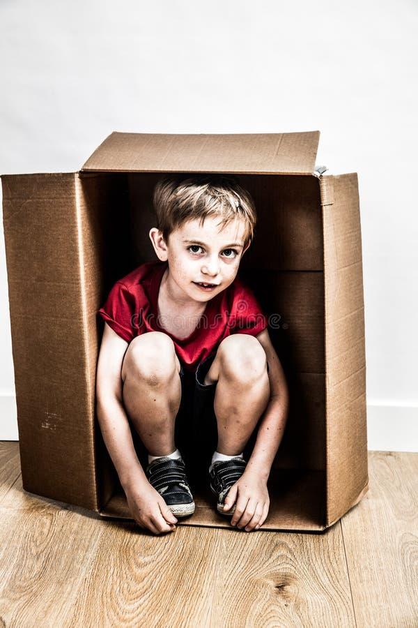 Kleine jongen in kartondoos het verbergen voor droevige bewegende dag stock fotografie