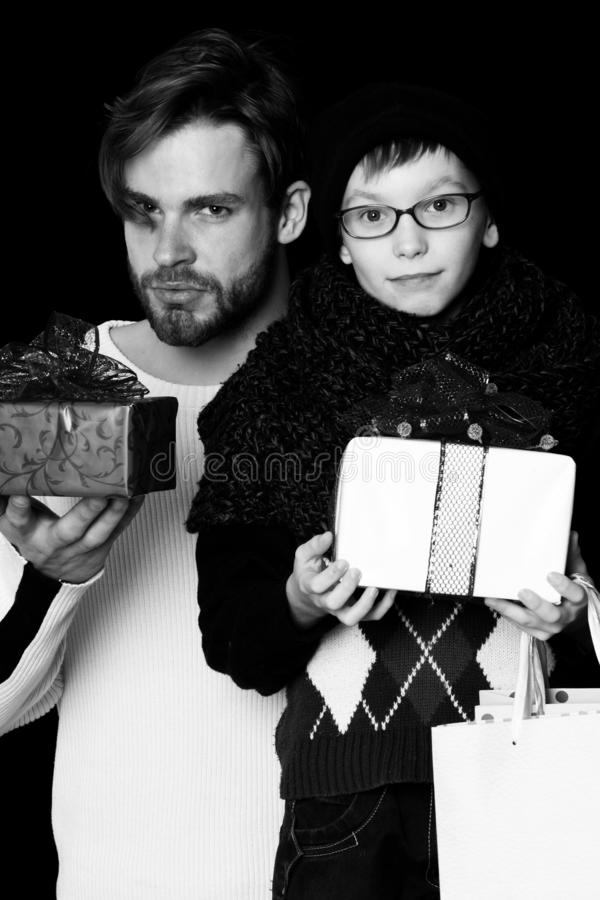 Kleine jongen of leuk nerdjong geitje in glazen, hoed en modieuze gebreide sjaal en knappe mens of gebaarde kerel op zwarte royalty-vrije stock afbeelding