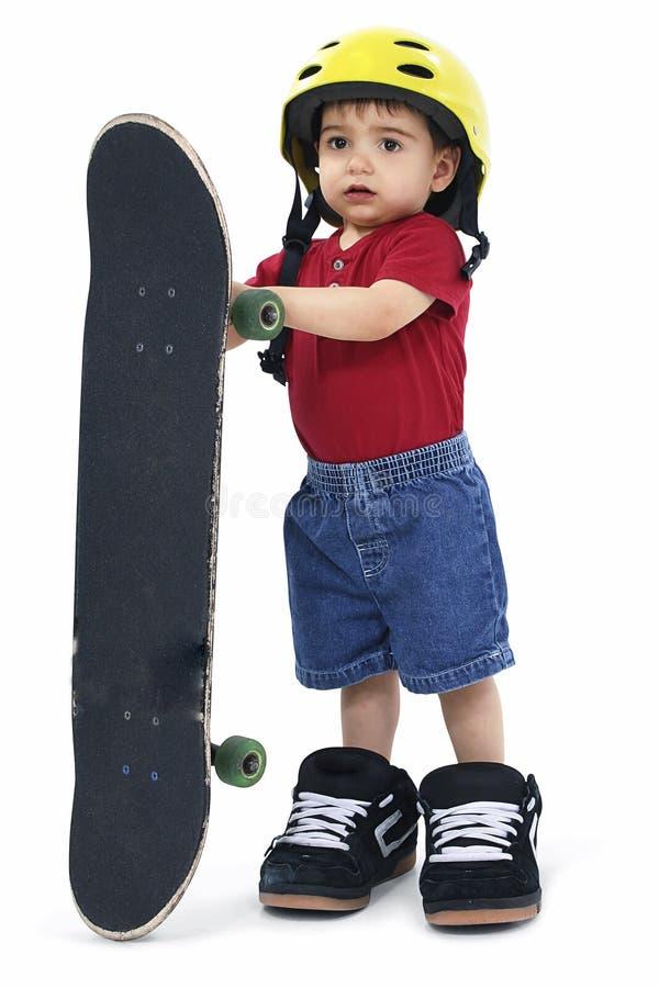 Kleine Jongen met het de Grote Schoenen en Skateboard van de Helm stock foto