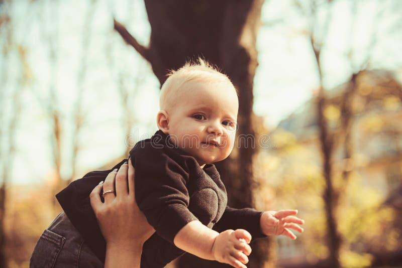 Kleine jongen in moedershanden op natuurlijke achtergrond Kind met blond haar openlucht De moederszoon geniet van idyllische dag stock afbeelding