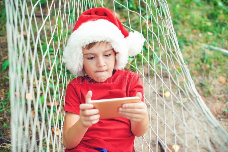 Kleine jongen speelt spelletjes op een smartphone in de buitenlucht Kind in Santa dat rusteert op hammock kerstvakantie Gelukkig  royalty-vrije stock afbeeldingen
