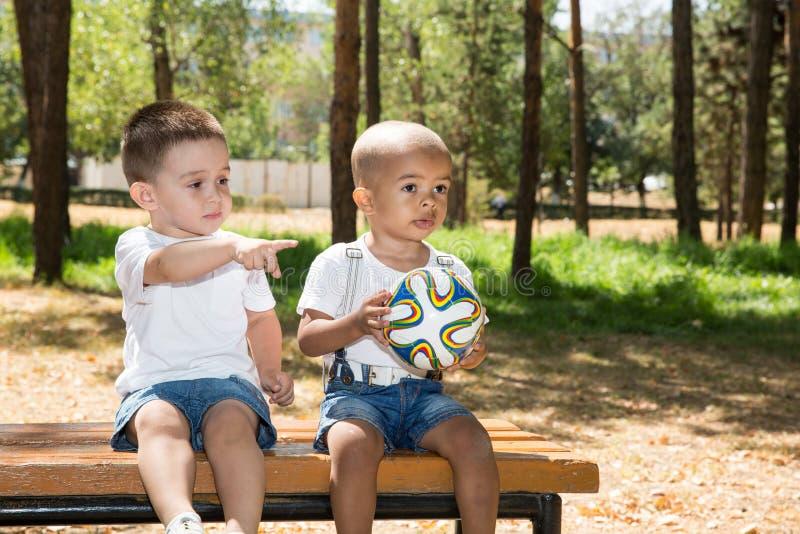 Kleine jongens: Afrikaanse Amerikaans en Kaukasisch met voetbalbal in park op aard bij de zomer stock fotografie