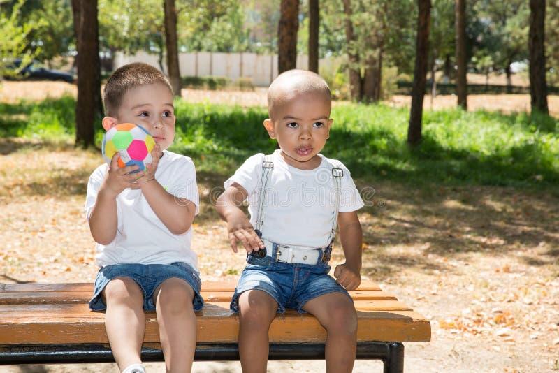 Kleine jongens: Afrikaanse Amerikaans en Kaukasisch met voetbalbal in park op aard bij de zomer stock foto's