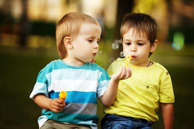 Kleine jongens die met bellen spelen stock foto's