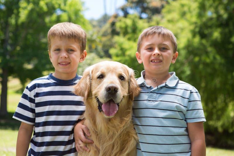 Kleine jongens met hun hond in het park stock afbeelding