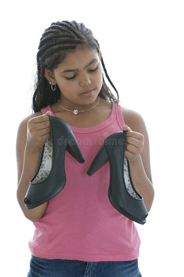 Kleine Jugendliche betrachtet Absatz-Schuh stockfotos