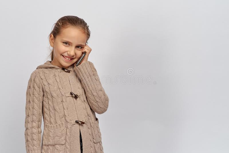 Kleine junge Dame in einer warmen braunen Strickjacke, die Kamera betrachtet und Telefon hält, Kind steht in einem angenehmen in  stockfoto