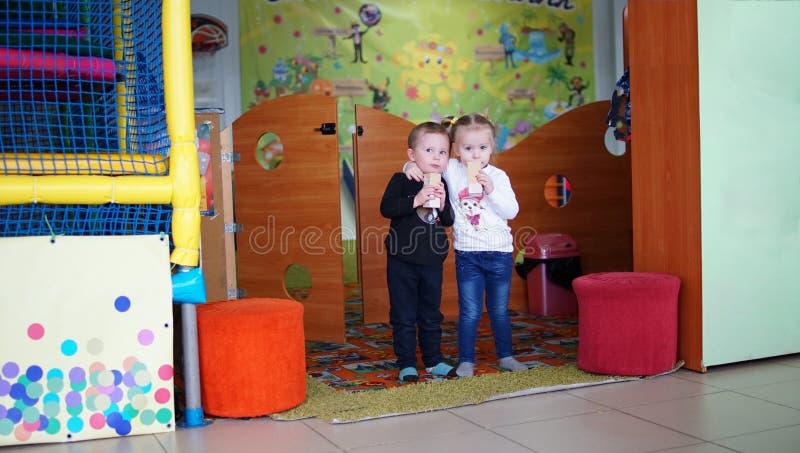 Kleine Junge und Mädchen, die im Kindergarten zusammen Saft trinken stockbilder