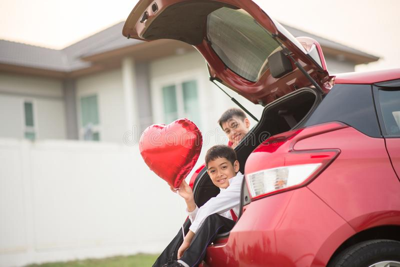 Kleine Jungen, die auf der Hintertür des Autos mit der Ballonherzhand sitzen lizenzfreies stockfoto