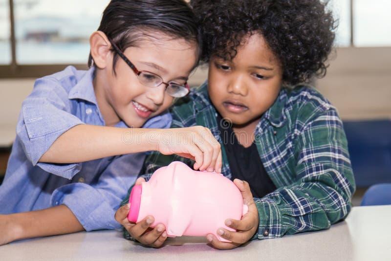 Kleine Jungen, die Geld in Sparschwein stecken lizenzfreie stockbilder