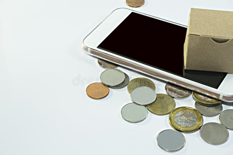 Kleine kartondoos op slimme telefoon met muntstukken op witte achtergrond royalty-vrije stock afbeeldingen