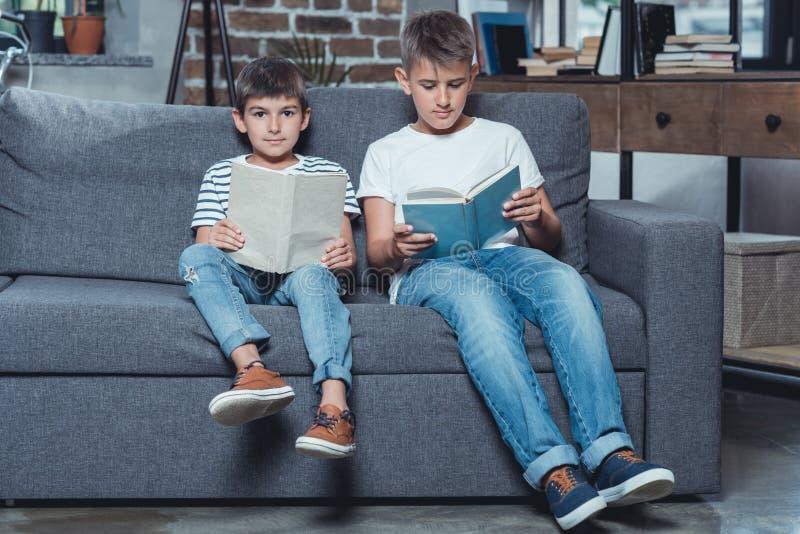 kleine kaukasische Jungenlesebücher beim Sitzen auf Sofa stockbild