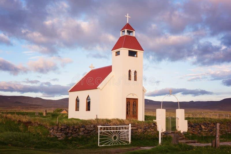 Kleine kerk tegen een mooie bewolkte hemelachtergrond, landschap in zonsonderganglicht, IJsland stock foto's