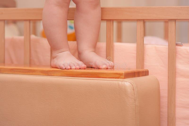 Kleine kindbenen dichtbij de wieg royalty-vrije stock afbeeldingen