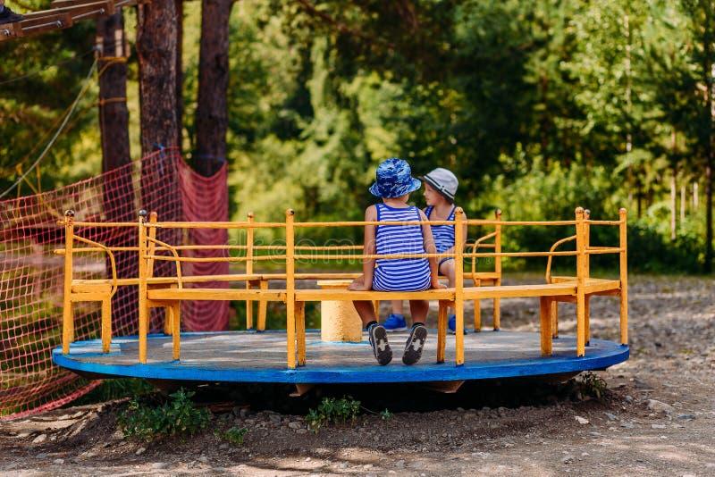 Kleine Kinder in den Sommerhüten und -t-Shirts, die auf einem großen Eisenkarussell im Park sitzen stockfotos