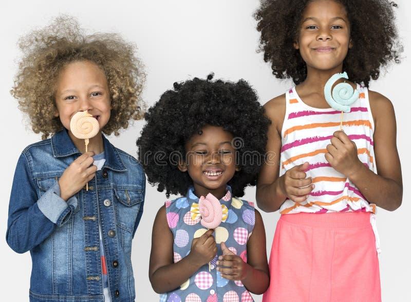 Kleine Kinder, die Lutscher-Süßigkeits-Lächeln essen lizenzfreie stockfotos