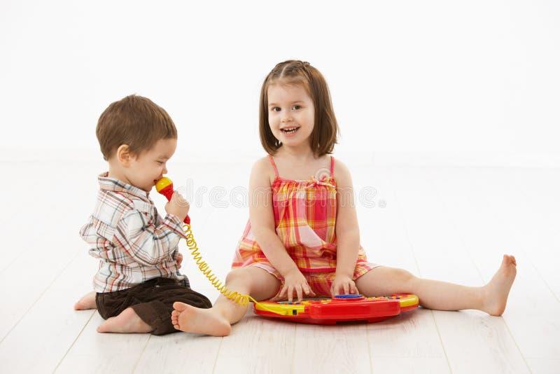 Kleine Kinder, die mit Spielzeuginstrument spielen stockfotos