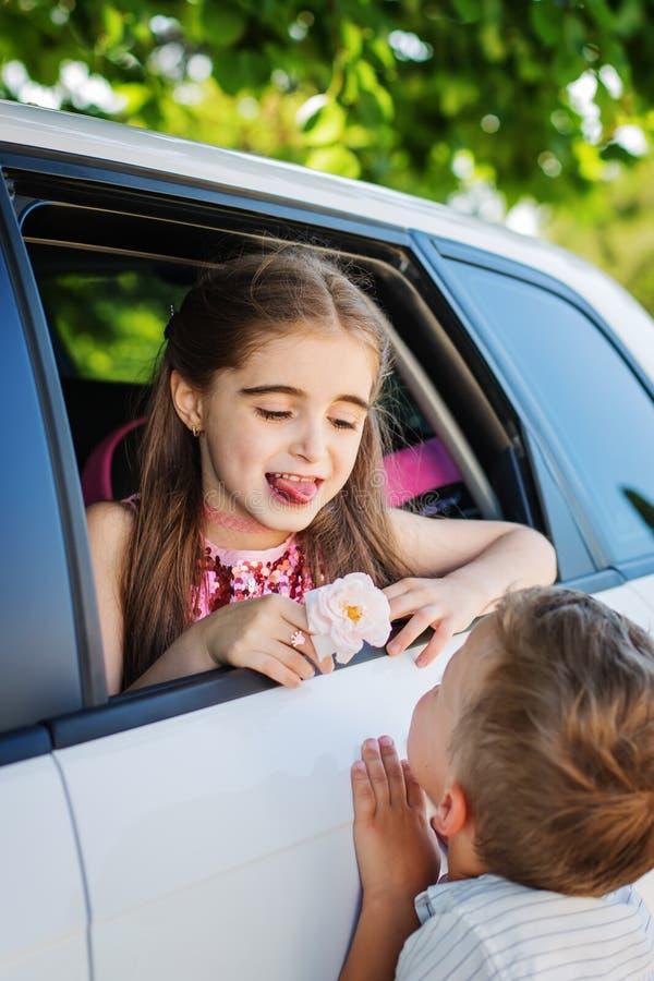 Kleine Kinder spielen, Junge gibt einem Mädchen eine Rose stockfotos