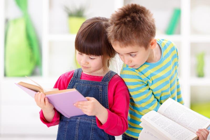Kleine kinderen die boeken lezen stock afbeeldingen