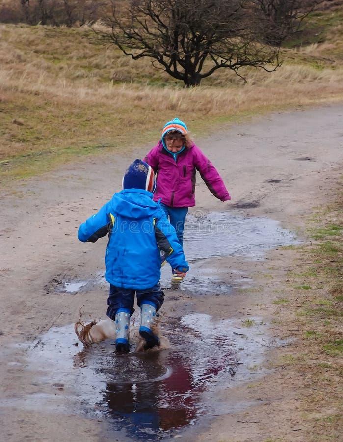 Kleine kinderen die in een modderige vulklei bespatten royalty-vrije stock foto