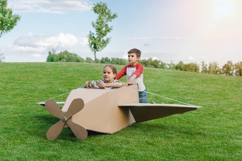 Kleine kinderen die met diy vliegtuig op groene weide in park spelen royalty-vrije stock afbeeldingen