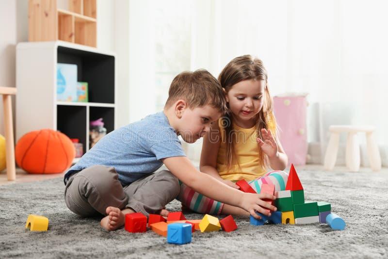 Kleine kinderen die met kleurrijke blokken spelen stock afbeeldingen