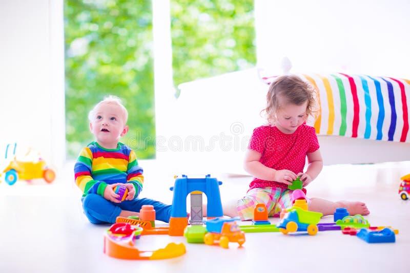Kleine kinderen die met stuk speelgoed auto's spelen stock afbeeldingen