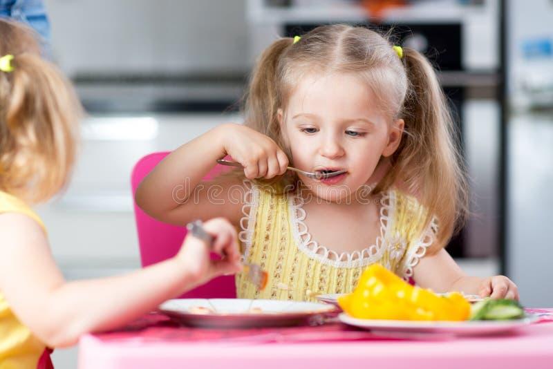 Kleine kinderen die voedsel eten bij opvang stock afbeelding