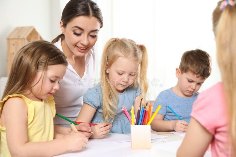 Kleine kinderen met de tekening van de kleuterschoolleraar bij lijst Het leren en het spelen stock afbeelding