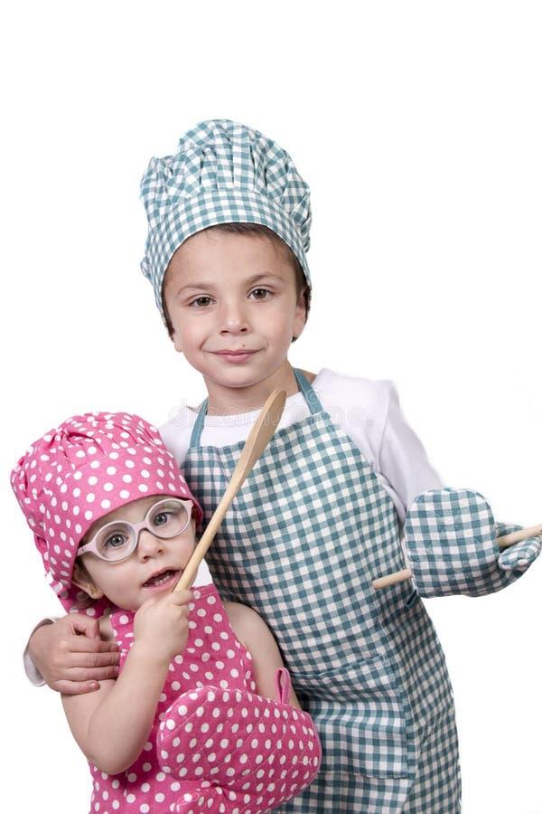 Kleine kinderen, met een houten lepel en kokkostuum stock afbeelding