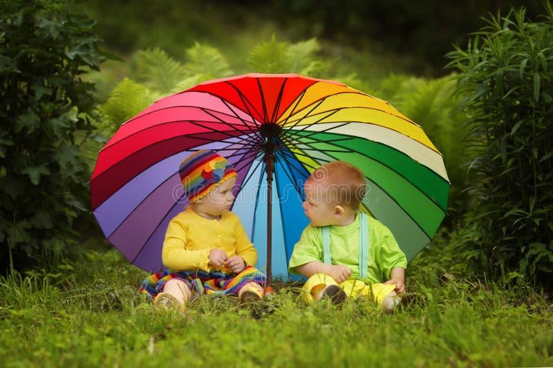 Kleine kinderen onder kleurrijke paraplu stock afbeeldingen