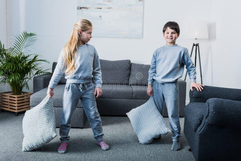 Kleine kinderen in pyjama's die hoofdkussenstrijd hebben thuis royalty-vrije stock foto