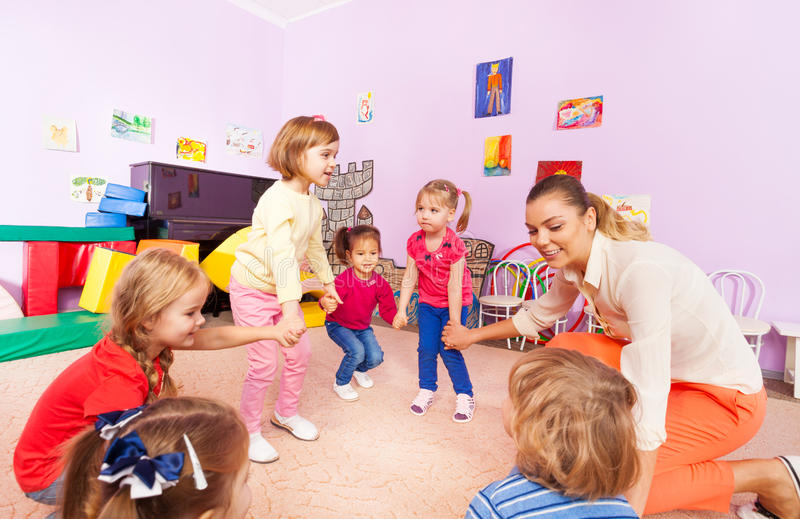 Kleine kinderenjongens, roundelay van het meisjes hurkende spel stock afbeeldingen