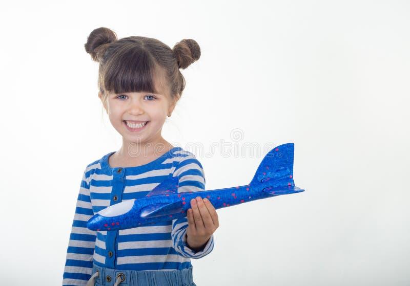 Kleine Kinderhände, die Flugzeug halten Tragendes gestreiftes Kleid des jungen Mädchens mit blauen Flugzeugen stockfoto