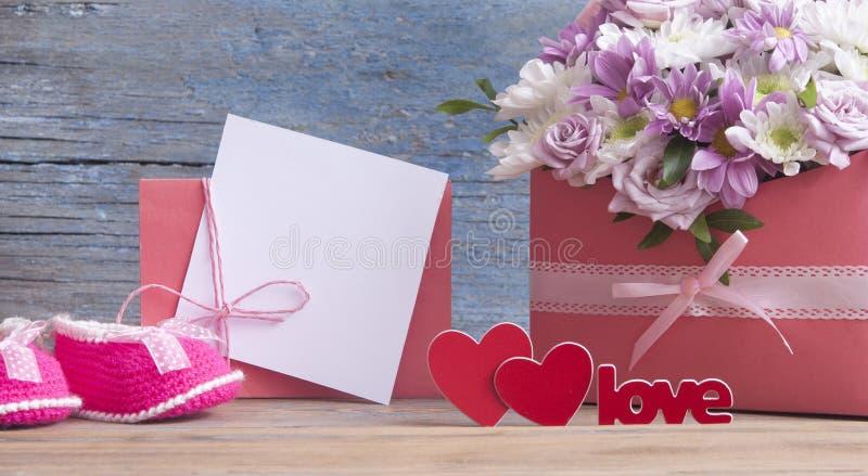 Kleine Kinderschuhe und schöner Blumenblumenstrauß auf dem hölzernen Vorsprung stockbilder